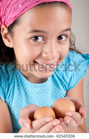 Young girl holding two eggs in her palm - stock photo
