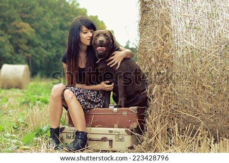 Young girl hugging her dog on meadow with hay - stock photo