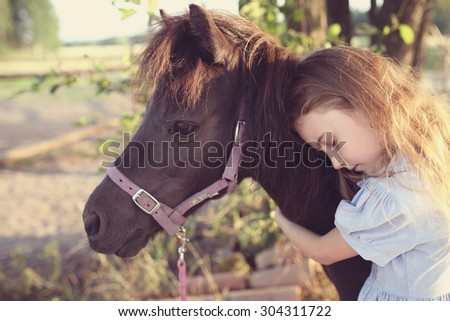 Young girl hugs a pony on a farm - stock photo