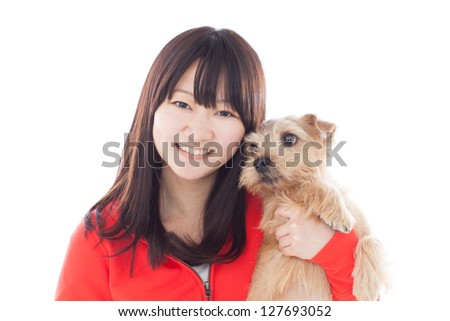 Young girl hugs Norfolk terrier dog, isolated on white background