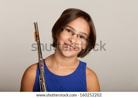 Young girl in a blue dress playing a flute - stock photo
