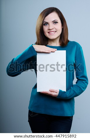 young girl in a blue t-shirt and jeans holding a poster, on a gray background - stock photo