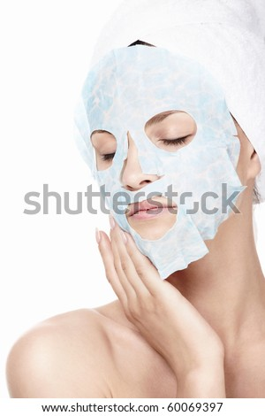 Young girl in a cosmetic mask on a white background - stock photo