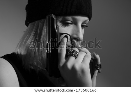 Young girl in a dark cap with a gun in his hand. Blonde with a gun. monochrome image - stock photo