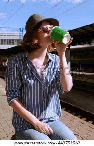 Young girl in a hat and sunglasses. Travel by train. Railroad station. A glass of coffee in her hands.