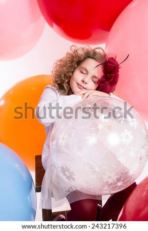 Young girl in a hat and white dress with her eyes closed against the background of large air rubber balls