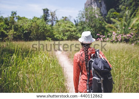 Young girl in a hat and with a backpack goes hiking on trail in the tropics - stock photo