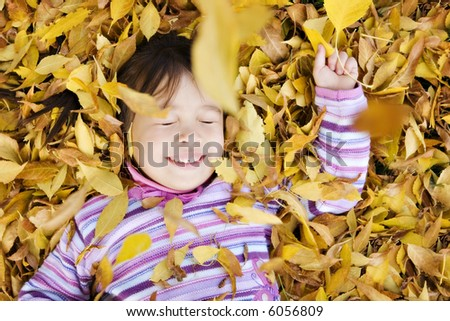 Young Girl in a Pile of Autumn Leaves, Eyes Closed as Leaves Fall on Her - stock photo