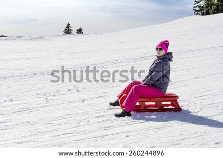 "Young girl in a pink hat with the words ""love"" and ski wear, on vacation, sitting on a red sled. - stock photo"