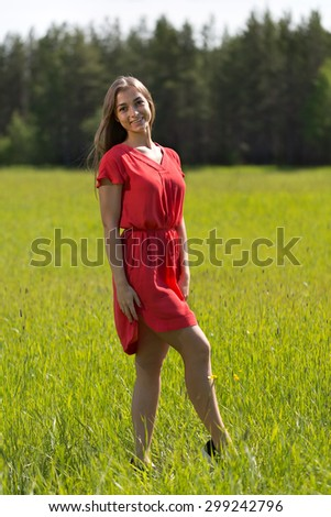 Young girl in a red dress in a field on a sunny day - stock photo