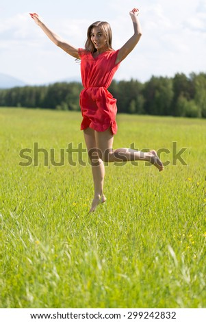 Young girl in a red dress jumping in a field on a sunny day. - stock photo