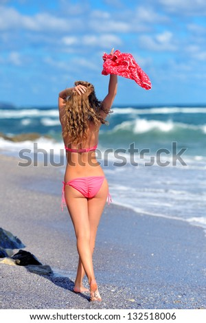 Young girl in a red dress on the ocean coast
