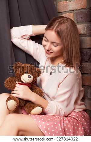 Young girl in a rose dress with bear toy. Studio photo - stock photo