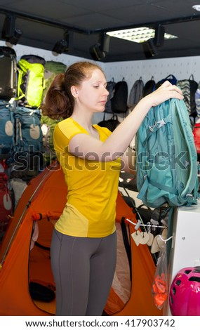 young girl in a specialty store for the tourism picks backpack.
