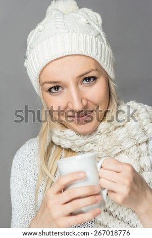 Young girl in a sweater with a white scarf and hat is holding a white cup and looking at camera - stock photo