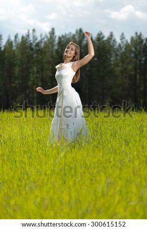 young girl in a wedding dress smiling and dancing in a field. - stock photo
