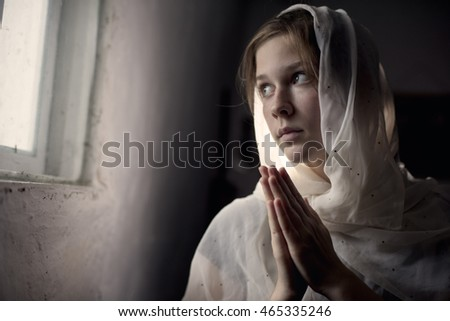 Young girl in a white scarf prays near a window.