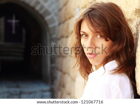 young girl in a white shirt is standing against a stone wall. In the distance can be seen the cross of the church. - stock photo