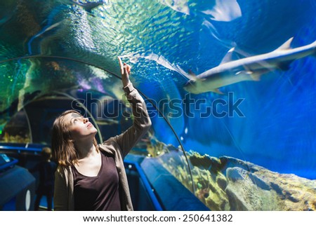 Young girl in aquarium tunnel with sharks - stock photo