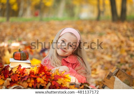 Young girl in autumn park with books, bouquet and little pumpkin