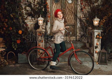 Young girl in autumn with red bicycle in hat - stock photo