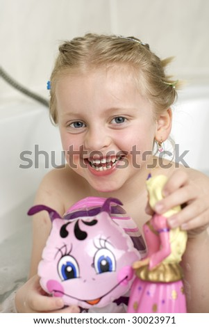 Young girl in bath tub with toys - stock photo