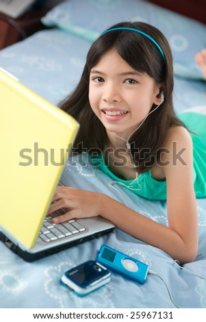 Young girl in bedroom using laptop