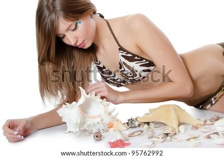 Young girl in bikini lays with seashells - stock photo