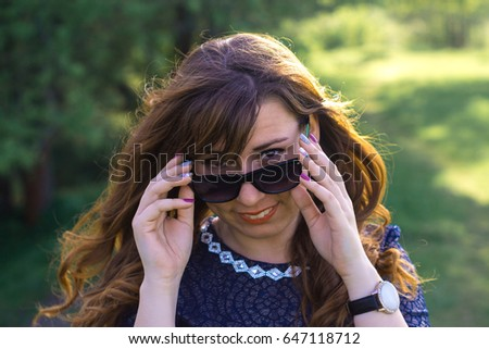 Young girl in black glasses on nature on a sunny day