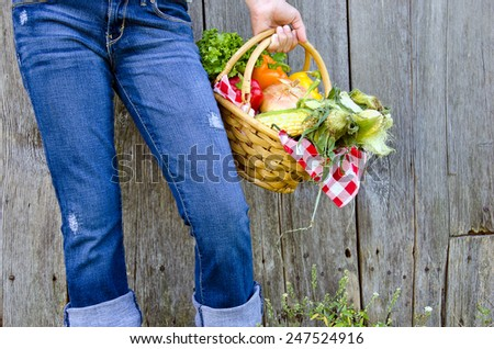 young girl in blue jeans holding a basket of fresh vegetables by old barn - stock photo
