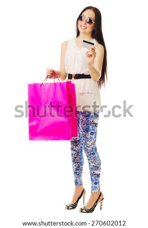 Young girl in blue pants with bags and credit card isolated - stock photo