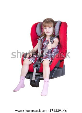 Young girl in car seat with thumbs up, isolated on white background - stock photo