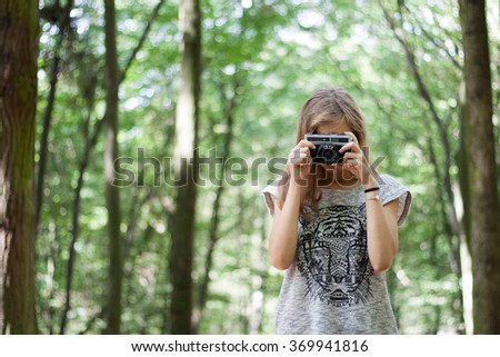 Young girl in casual clothes with old retro vintage camera photographing in forest. Brown hair, long legs, slim body. - stock photo