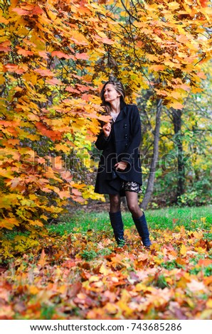 Young girl in classic black coat and blue boots walks in the Park . Autumn Park , green , red and yellow leaves lie on the ground. The girl has long black hair and slim figure .