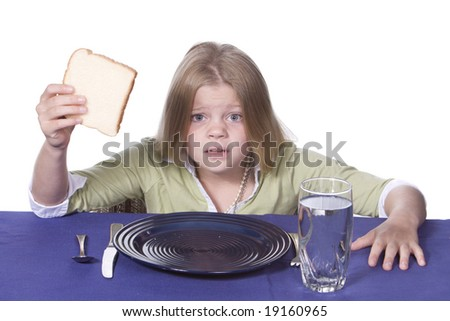 Young girl in disbelief about her bread and water dinner. - stock photo