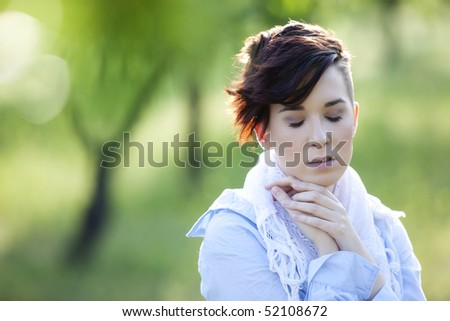 Young girl in emotional gesture with eyes closed.
