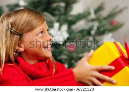 Young girl in front of the Christmas tree showing the world the present she received - stock photo