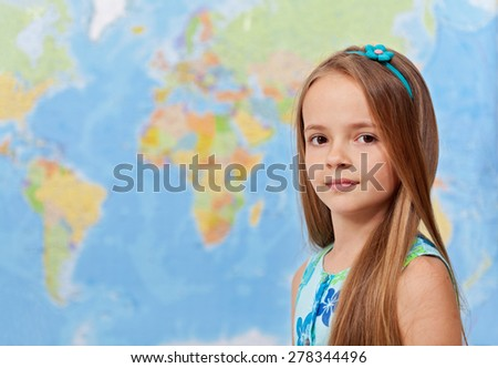 Young girl in front of world map - in geography class, with copy space - stock photo