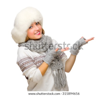 Young girl in fur hat shows welcome gesture isolated - stock photo