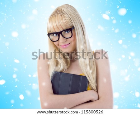 Young girl in glasses hugging her book tightly. Snowflakes - stock photo