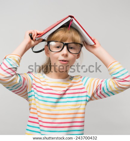 young girl in glasses with a book on her head - stock photo