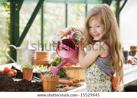 Young girl in greenhouse putting plant in pot - stock photo