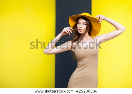 Young girl in hat posing by the yellow wall
