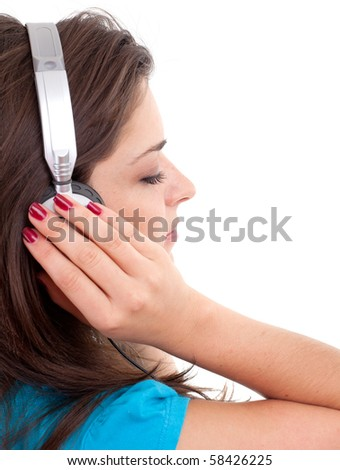 young girl in headphones listening music from mp3 player