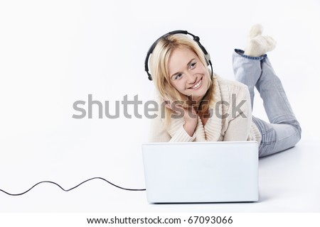 Young girl in headphones with a laptop on a white background - stock photo