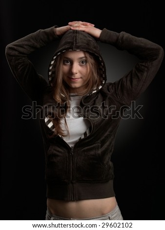 Young girl in hood is smiling against a dark background - stock photo