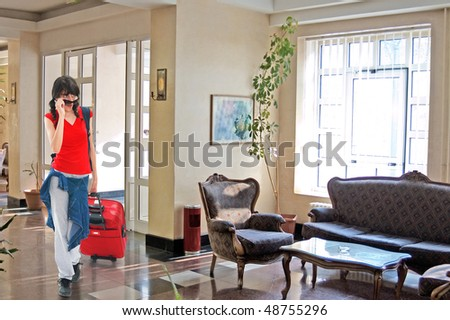 Young girl in hotel lobby with huge luggage - stock photo