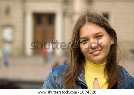 young girl in jeans jacket laughing