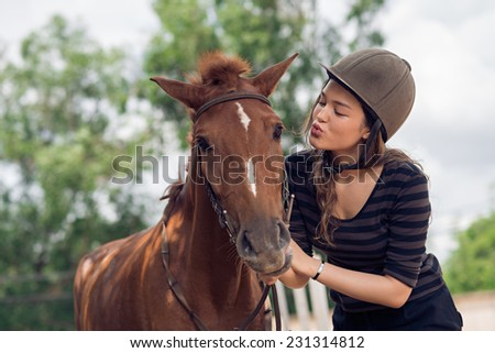 Young girl in jockey cap kissing her horse - stock photo