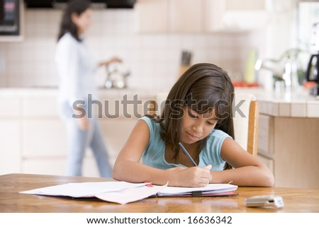 Young girl in kitchen doing homework with woman in background - stock photo